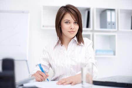 Chân dung của một người phụ nữ trẻ xinh đẹp làm kinh doanh mỉm cười một số giấy tờ trong văn phòng sáng