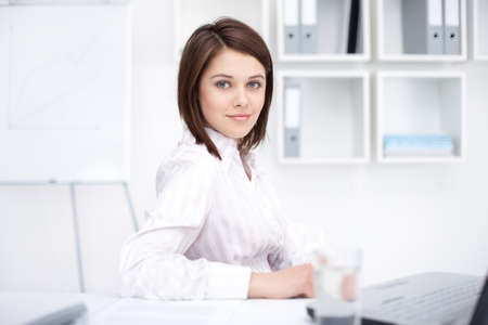 business woman: Portrait of beautiful young business woman sitting at desk at office  Stock Photo