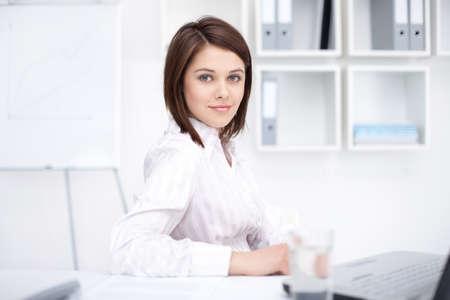 mujer sentada: Retrato de mujer de negocios hermosa joven sentado en el escritorio en la oficina