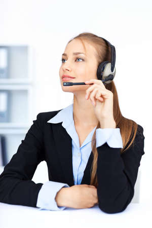 Portrait of pretty young female operator sitting at office desk with headset  Stock Photo - 15919134