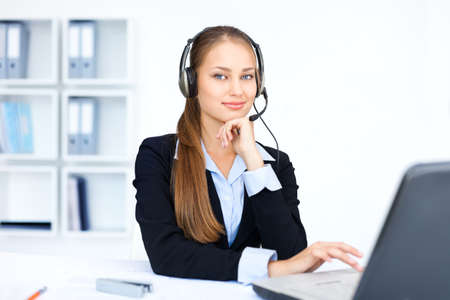 Portrait of pretty young female operator sitting at office desk with headset  Stock Photo - 15896868