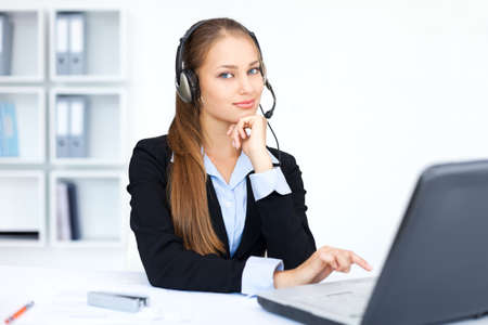 Portrait of pretty young female operator sitting at office desk with headset Stock Photo - 15896877