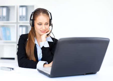 Portrait of pretty young female operator sitting at office desk with headset  Stock Photo - 15896826