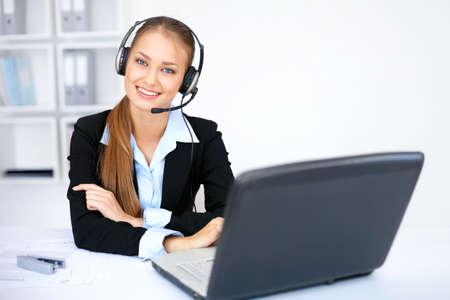 Ritratto di bella giovane operatore femminile seduta alla scrivania con auricolare