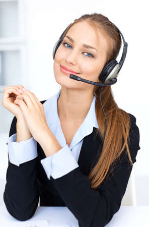 Portrait of pretty young female operator sitting at office desk with headset Stock Photo - 15919111