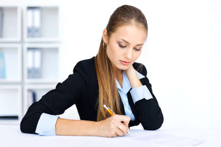 Portrait of a beautiful young business woman doing some paperwork in office  Stock Photo - 15896885
