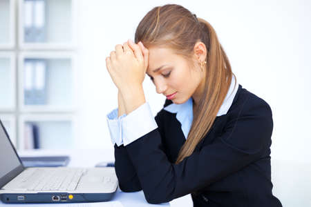 Portrait of tired young business woman with laptop computer at the office Stock Photo - 15919069