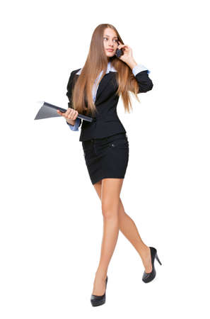 Portrait of a beautiful business woman talking on the cell phone and holding a folder while walking on white background