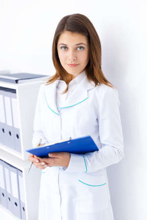 Portrait of young female doctor holding clipboard in hospital photo