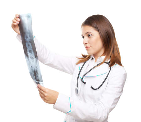 Young female doctor looking at the x-ray picture of spinal column isolated on white background photo