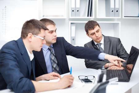 Squadra di giovani uomini d'affari che lavora al computer portatile insieme in un ufficio Archivio Fotografico