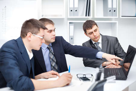 consultant: Team of young business men working at laptop together in a office Stock Photo