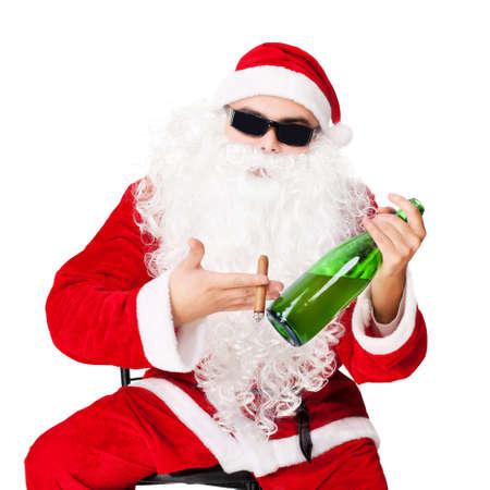hombre fumando puro: Papá Noel que se sienta en una silla con gafas de sol sostiene una botella de champaña y fumando un cigarro aislado sobre fondo blanco Foto de archivo