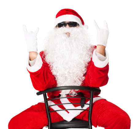 Man in Santa Claus clothes sitting in a chair showing the rocker hand sign on a white background Stock Photo