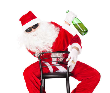 drunk party: Santa Claus sitting in a chair wearing sunglasses holds a bottle of champagne and smoking a cigar isolated on white background