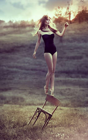 beautiful girl balances on back of chair outdoors  Artwork photo
