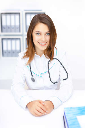 Portrait of young female doctor sitting at desk in hospital Stock Photo - 17475711