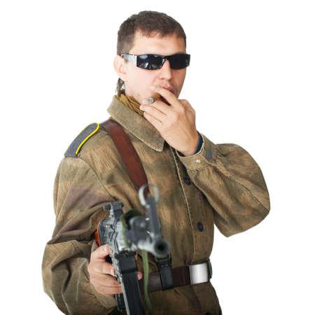 hombre fumando puro: Soldado con gafas de sol con la ametralladora fumando un cigarro aislado sobre fondo blanco