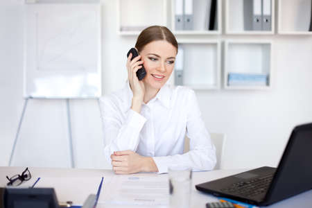 beautiful young business woman sitting at office desk and talking on cell phone  photo