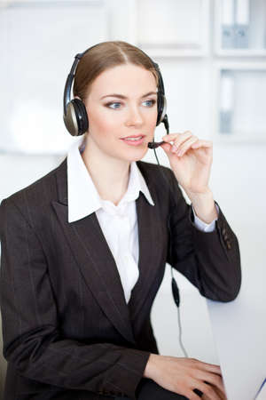 Portrait of pretty young female operator sitting at office desk with headset  Stock Photo - 17478123