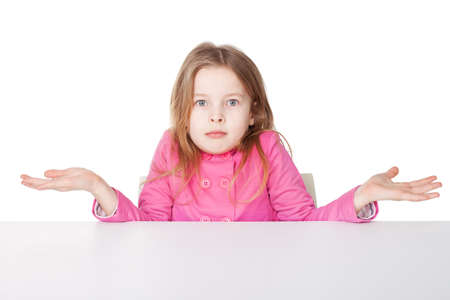 Cute little girl in red shirt shrugging her shoulders while sitting at table isolated on white background