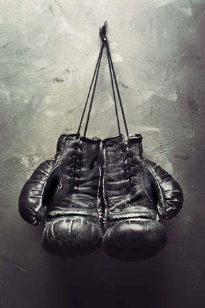 leather glove: old boxing gloves hang on nail on textured wall - Retirement concept