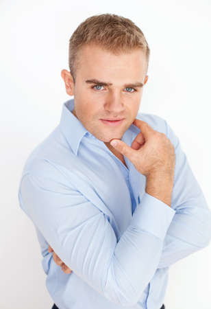 Portrait of young business man holding hand up to chin with arms folded on white background photo