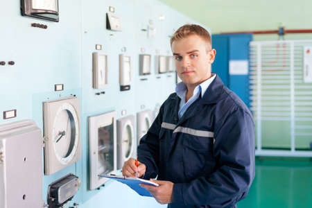 Portrait of young engineer taking notes at control room photo