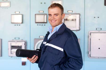 Kỹ sư trẻ cầm ống với bản thiết kế tại phòng điều khiển