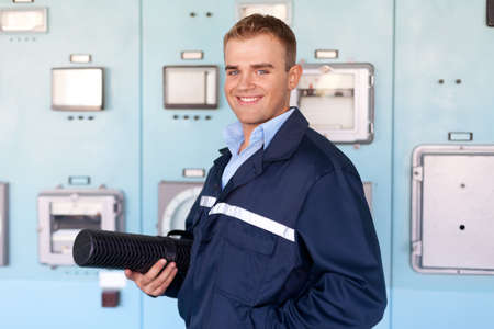 Young engineer holding tube with blueprints at control room