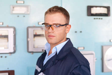 technical service: Young engineer wearing a safety glasses at control room