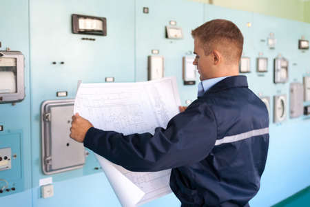 Young engineer looking at blueprints at control room