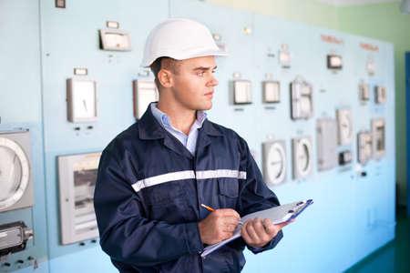 panel de control: Retrato del ingeniero joven sonriente que toma notas en sala de control