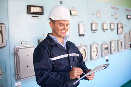 young engineer: Portrait of young smiling engineer taking notes at control room
