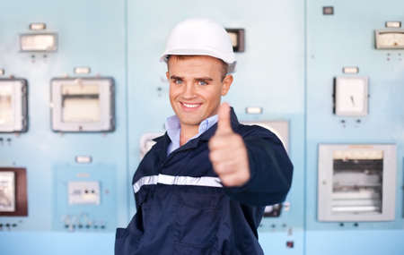 protective workwear: Portrait of young engineer with thumbs up at control room Stock Photo