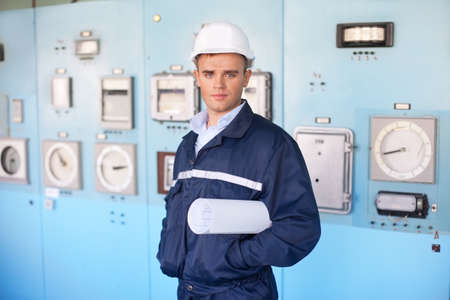 Portrait of young engineer with helmet and blueprints in control room photo