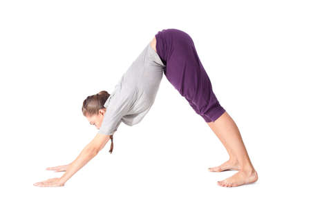 Young woman doing yoga exercise Downward-Facing Dog. Isolated on white background photo