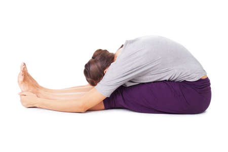 Young woman doing yoga asana seated forward bend Paschimottanasana. Isolated on white background Stock Photo