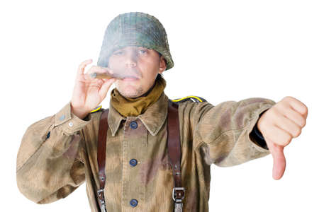 Soldier smoking a cigar and gives a thumb down isolated on white background photo