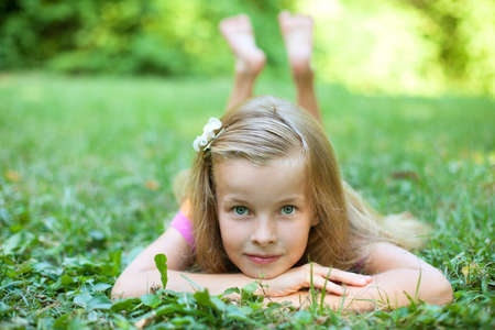 Beautiful little girl is lying on the green grass photo