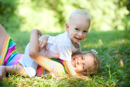 kids hugging: Brother and sister playing on the grass in summer