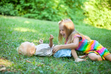 Brother and sister playing on the grass photo