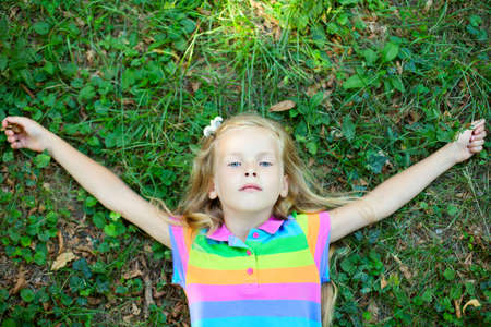 Top view of little funny girl lying on grass