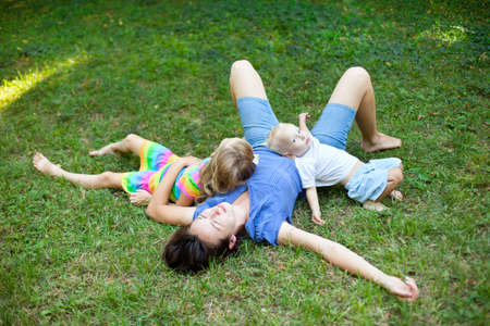 Joyful family enjoying themselves laying on the grass in a park photo