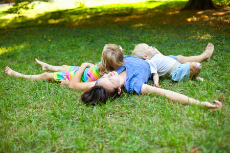 girl lying: Joyful family enjoying themselves laying on the grass in a park