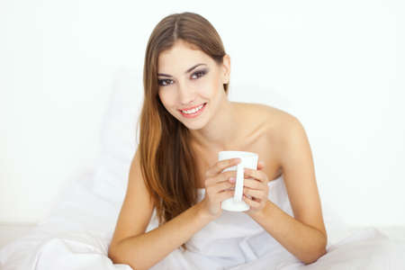 Beautiful smiling young woman in bed with a cup of coffee photo