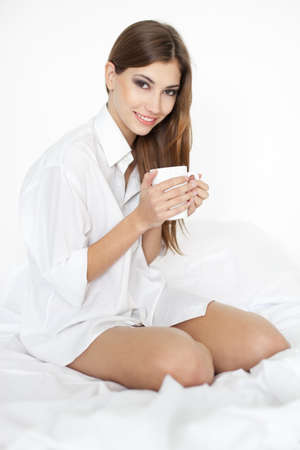 Beautiful smiling young woman on bed with a cup of coffee photo