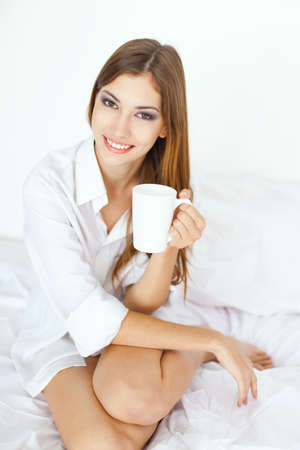 Beautiful smiling young woman in bed with a cup of coffee Stock Photo - 18353613