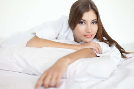 Beautiful happy smiling young woman in large shirt on bed photo