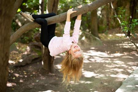 niño escalando: Chica ?ute poco en broma cuelga de una rama de un árbol